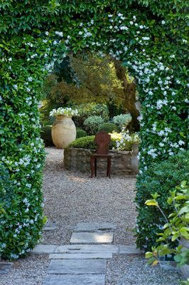 DESIGNER MICHEL SEMINI, PROVENCE, FRANCE. VIEW THROUGH DOORWAY WITH TRACHELOSPERMUM JASMINOIDES TO GRAVEL COURTYARD WITH TERRACOTTA CONTAINER AND ORNATE METAL SEATS.