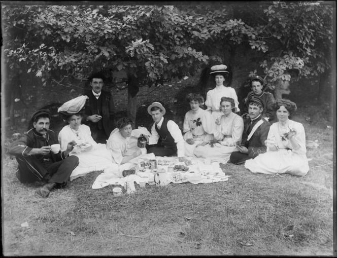 Group picnicking, showing unidentified men, some in military uniforms, and women in tea dresses, sitting around a cloth laid with food, possibly Christchurch district 1910