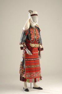 Νυφική φορεσιά από την Πυλαία Θεσσαλονίκης  Γιορτινή ενδυμασία Καπουτζήδας. Το χρώμα, τα κεντήματα και η ονομασία ορισμέ- νων εξαρτημάτων της ενδυμασίας, μας πληροφορούν για τον οικογενειακό και θρησκευτικό κύκλο της ζωής της γυναίκας. Η ενδυμασία έχει λευκό πουκάμισο και μπλε σκούρο σαγιά, υφαντή ποδιά ενώ στη μέση φοριέται το ζωνάρι με το κλεικουτήρι. Χαρακτηριστικό του νυφικού κεφαλόδεσμου είναι το σουργούτς ή λούδι που στερεώνεται στο λευκό μαντήλι.;   The color, embroidery and the names…