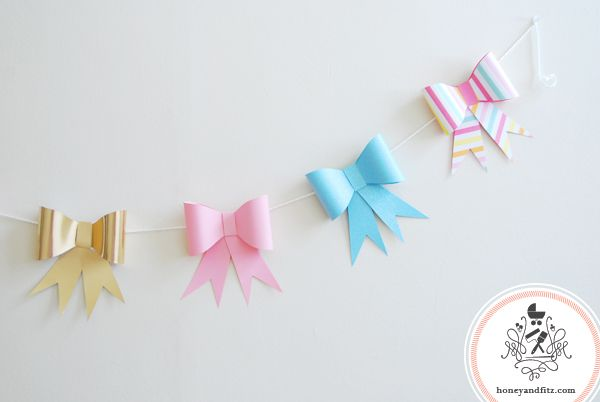 DIY Paper Bow Garland by Honey and Fitz. By cutting out a bow template on cardstock, you too can make this darling banner for your next gathering!  You can download the template from the blog.  For a large selection of double-sided cardstock, visit www.cardstockshop.com.
