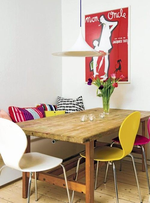 sala de jantar pequena com mesa rústica e banco com almofadas coloridas