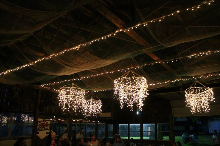 The Ceiling Is Covered In Rows Of Tulle And Christmas