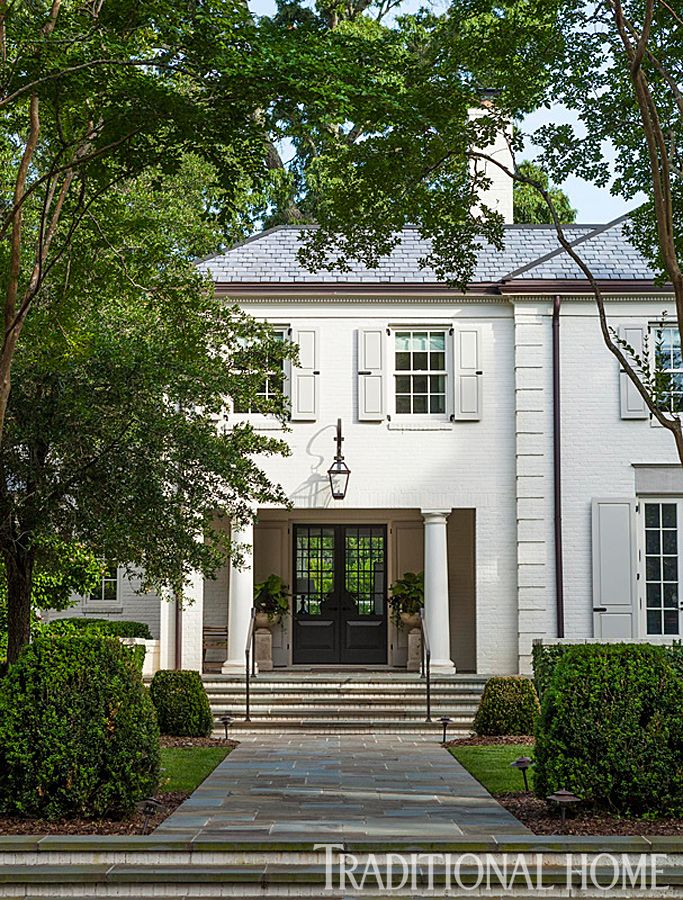 A wide walkway leads up to the front door of this charming Charleston home. - Traditional Home ® / Photo: John Bessler