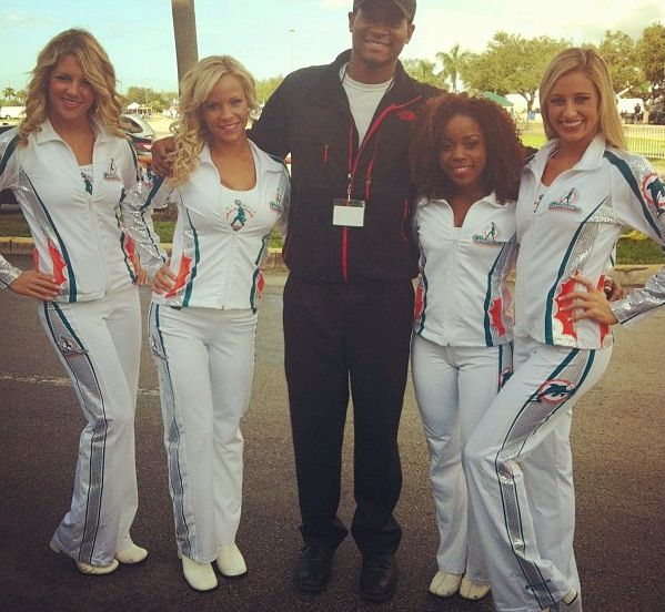 4 Miami Dolphin Cheerleaders posing with a fan in the pants and jackets we made for them!  :) #cheerleaders #cheerleading #uniforms #4cheerleaders #miamidolphins #miamidolphinscheerleaders #blonde
