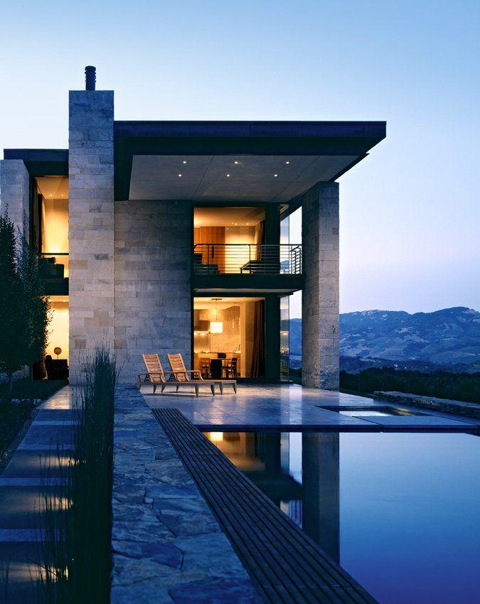 Casa com Arquitetura moderna com a junção da alvenaria, pedra, madeira e vidro, com a iluminação amarelada e natural.