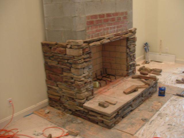 light colored bricks inside stacked stone fireplace