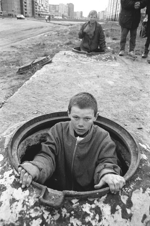 St. Petersburg, Russia A homeless boy climbing out of his underground hiding place. He and other homeless kids sleep on top of the hot water pipes under the street on the outskirts of the city. Almost all the kids are addicted to sniffing glue. Published in Washington Post. by Paul Christopher Miller.