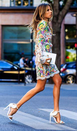 Une robe courte aux couleurs estivales avec des escarpins blancs et une petite pochette argentée.