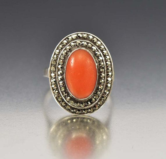 Throughout time, coral has been the stone to attract love and prosperity. This lovely Art Deco era silver ring with rows of sparkling marcasite and a natural coral gemstone center has all the earmarks of the perfect love token anniversary gift. The oval coral gemstone is band wrapped and open back surrounded by two rows of sparkling marcasite. An engraved design forms the shoulders with the band smooth. Simple and elegant!  Materials: 835 Silver Gemstones: Coral - 13.5mm by 9.5mm, Marcasite…