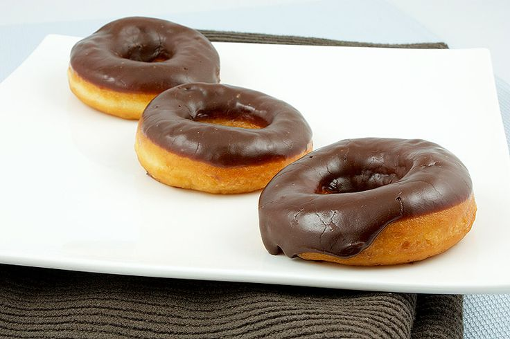 A photo of 3 chocolate glazed doughnuts on a white plate placed on a brown tea towel.