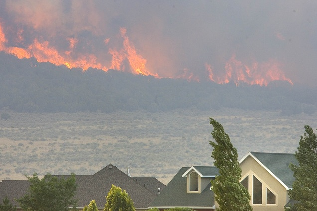 Wildfires in Utah already have cost 50 million dollars, burning more than 422,000 acres around the state. This photo shows the lightning-caused Pinion Fire burning behind homes in Eagle Mountain earlier in August. (Paul Fraughton   The Salt Lake Tribune)