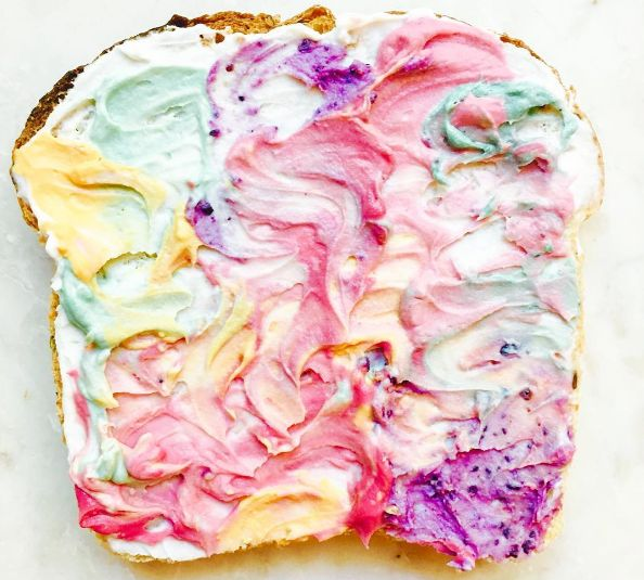 This is unicorn toast, the newest brunch food trend. Started by food photographer and stylist Adeline Waugh, it's basically normal toast with cream cheese which has been coloured in all sorts of pastel colours.