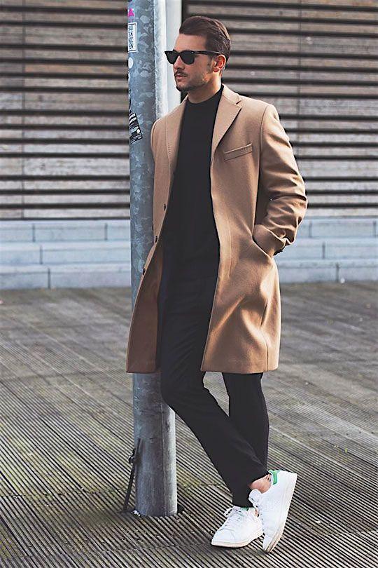 Acheter la tenue sur Lookastic: https://lookastic.fr/mode-homme/tenues/pardessus-brun-clair-pull-a-col-rond-noir-pantalon-chino-noir/16991 — Pull à col rond noir — Pardessus brun clair — Pantalon chino noir — Baskets basses en cuir blanches