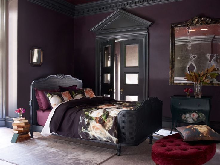 Rich and deep colours to give a sumptuous feel in the bedroom with a floral printed bedding set and a dark bed frame.