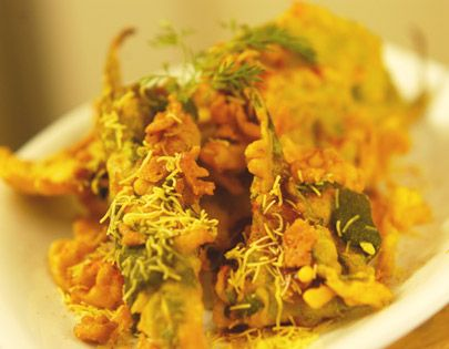Palak Pakore Ki Chaat - Batter fried spinach leaves topped with green chutney and sweet chutney, sprinkled with chaat masala.