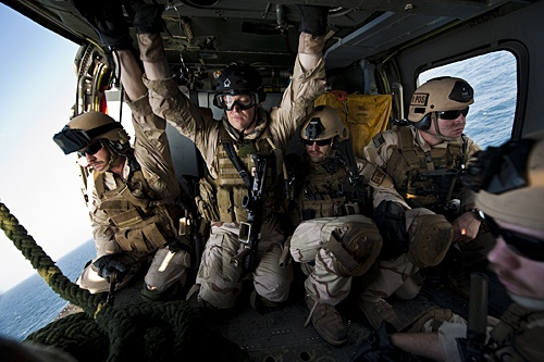 US Navy EOD prepare to rappel down from an MH-60S Knighthawk assigned to the carrier USS John C. Stennis during a training operation in the Arab Sea.