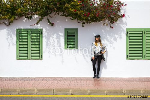 Young girl standing against classic spanish building facade with coloured shutters