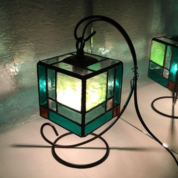 受注制作ご注文頂いてから制作致しますので2週間程お時間頂戴します。ステンドグラスの技法で制作しています。アップルグリーンをメインにエメラルドグリーン、ミントグリーンで引き締めたサイコロ型のハンギングランプです。淡い色合いが自然光でもお楽しみ頂けます。ミニタイプですので玄関や寝室など 場所を問わずに飾って頂けます。電球、ハンギング込みの価格です。サイズ ハンギング高さ23㎝ ランプ9㎝四方形『特別企画2017』