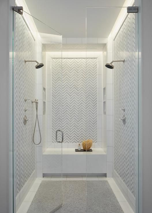 Facing Each Other Polished Nickel Shower Heads Are Mounted To A White And Gray Herringbone Backsplash Framed By Border Tiles That Also Accent