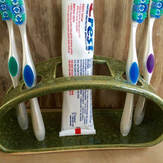 Main levée en céramique brosse à dents et dentifrice titulaire  Porte brosse à dent/dentifrice a été tourné à la main et ensuite modifié pour accueillir 4 brosses à dents et un tube de dentifrice. Brosses à dents parfaitement dans autour des ouvertures de chaque côté dune ouverture rectangulaire, conçue pour le tube de dentifrice. La conception ouverte permet un nettoyage facile (lave-vaisselle) et les trous sont suffisamment grands pour accueillir la plupart des brosses à dents manuelles…