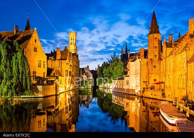 Twilight scenery in Bruges with water canal and Belfort tower. Flanders, Belgium.