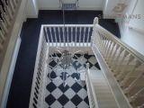 Witte dichte hardhouten trap. Met een bijpassende vloer levert dit een prachtige hal op.