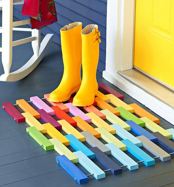 Bright yellow wellies on a rainbow-coloured doormat beside a bright yellow door - perfect