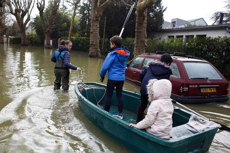 VILLENNES SUR SEINE, FRANCE -  A woman uses a dinghy boat to carry children through a flooded street of Villennes sur Seine, west of Paris, on Jan. 30. Floodwaters peaked in Paris on Monday and were threatening towns downstream as the rain-engorged Seine River winds through Normandy toward the English Channel.  Week in Weather: FEB 2 - February 2, 2018.