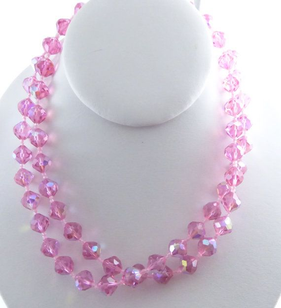 Pink Faceted Glass 2 Strand Beaded Necklace with Crystal Clasp. Set in silver tone metal. Fancy box clasp.The faceted glass beads have an AB (borealis) finish. Measures 16 in length including the clasp. Very good vintage condition with wear to the back of the clasp. For more