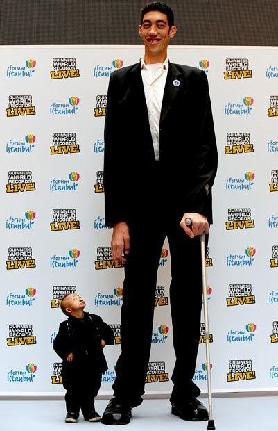 The world's tallest man, Sultan Kosen (8 ft 1 in), and the shortest man in the world, He Pingping (2 ft 5 in)