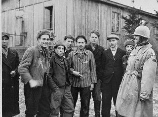 A U.S. army officer (far right) poses with survivors of the Ohrdruf camp, a subcamp in the Buchenwald camp system.