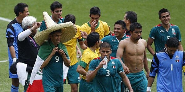 Mexico's double goal scorer Oribe Peralta, front left, wears a sombrero hat and a national flag while celebrating with team mates after their victory over Brazil in their men's soccer final gold medal match at Wembley Stadium during the London 2012 Olympic Games. (Photo by Paul Hanna/Reuters)