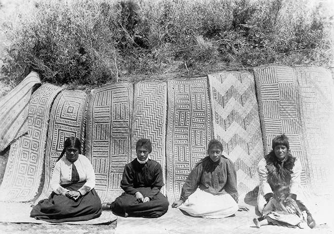 A collection of intricate and beautiful floor mats woven for Te Rauru meeting house at Whakarewarewa, Rotorua, are seen in this photo from about 1898. In front are some of the Te Arawa women who wove the mats.