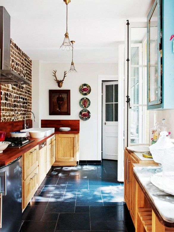 Rustic French kitchen with brick wall and blue tiled floor.
