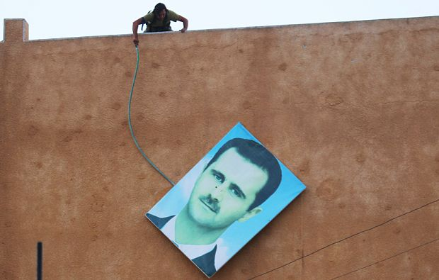 An al-Nusra rebel takes down a picture of Syria's President Bashar al-Assad in Ariha, after a coalition of insurgent groups seized the area