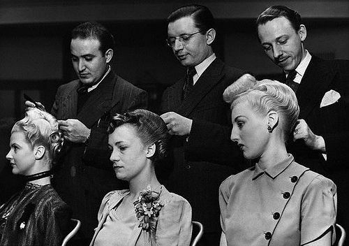 Three 1940s hairdressers and their models hard at work during a hairdressing competition.