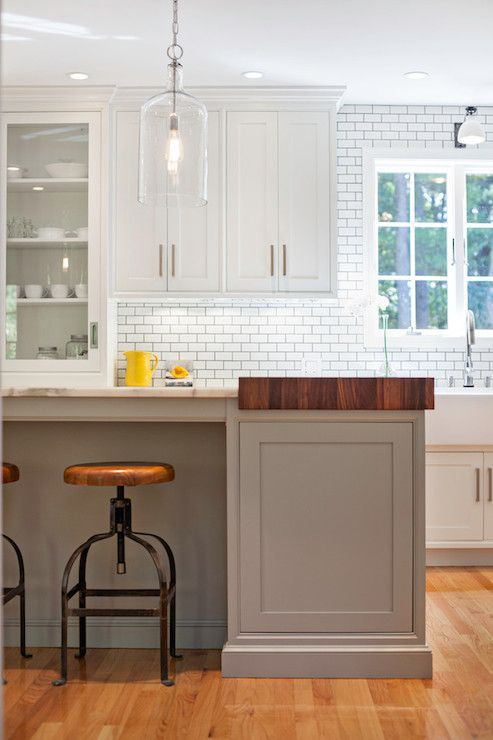 White and gray kitchen with gray island lined with World Market Twist Swivel Stools topped with a Calacatta Marble counter with attached prep island topped with butcher block illuminated by an Home Decorators Collection Capri 1 Light Pendant.