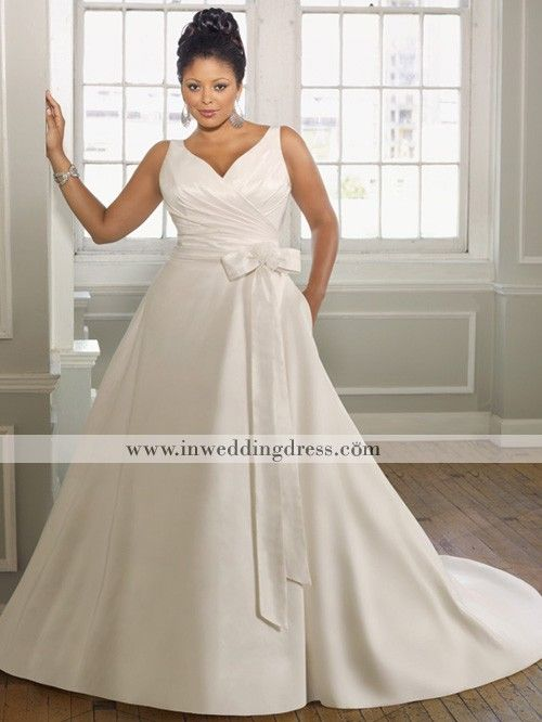 Vintage wedding dress features in radiant taffeta. Waist tie-sash and detachable flower. Hidden back zipper with covered buttons