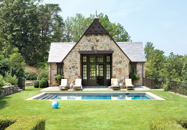 Stone, slate roof, black window frames, grass and pool