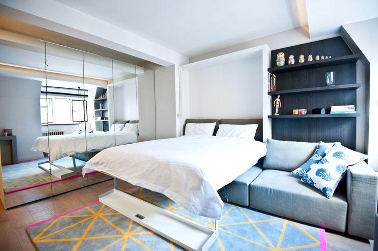 Кровать здесь самая что ни на есть полноценная — двуспальная, большая и высокая. Отделяется она от стены лёгким движением руки и «приземляется» прямо на диван. К слову, спинка самого дивана так же легко опускается вниз. На всё про всё — несколько секунд. Высший пилотаж — сделать минимализм уютным: здесь на тепло родного дома работает деревянный фактурный пол, ковёр, свечи, имитация каминного портала и милейшие матрёшки в нише.