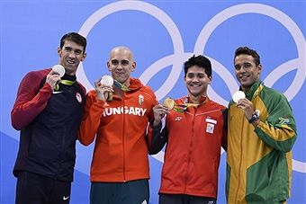 TOPSHOT - Singapore's Joseph Schooling(2ndR) poses with silver medallists (fromL) USA's Michael Phelps, Hungary's Laszlo Cseh and South Africa's Chad Guy Bertrand Le Clos after he won the Men's 100m Butterfly Final during the swimming event at the Rio 2016 Olympic Games at the Olympic Aquatics Stadium in Rio de Janeiro on August 12, 2016. / AFP / GABRIEL
