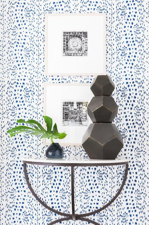 Chic foyer features walls clad in Brunschwig & Fils Les Touches Blue Wallpaper lined with a half moon marble top console table and stacked art.