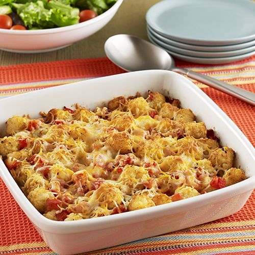 A side dish recipe for cheesy taco bake casserole with potato puffs, zesty tomatoes and taco seasoning topped with shredded cheese