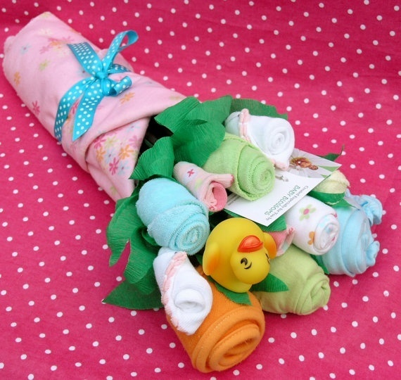 Baby clothes bouquet.  Can mix in things like shampoo bottles, wash cloths, binkies, small books, coupons or tickets or gift certificates to a takeout restaurant etc..  Looks best mixed with fake leaves and flowers.