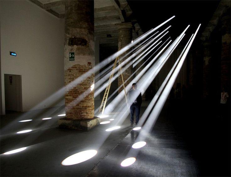 intense light beams from twenty spotlights extend diagonally across the dark…