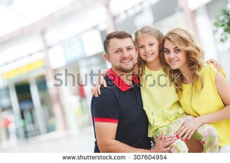 Mother, daughter and father in shopping mall. Family with shopping bags having…