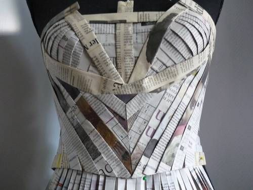 I love how coloured parts of a newspaper have been added in to this garment it makes it a bit more interesting. The pin tuck effect on the body is really great. I also like how there is a completely different paper around the boob outline to make the garment stand out even more. Although you can't see a full body shot of the garment you can see that there it a skirt with layers of paper, i would of maybe kept the skirt straight as this would help to make the top part stand out more.