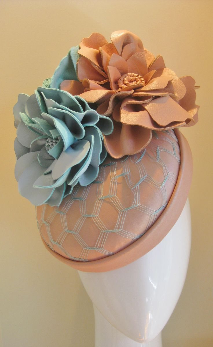 Perfect pastel posey. 3 leather blooms in peach and pale blue are atop this peach leather button hat. The button is covered in pale blue(almost aqua) vintage veiling for texture. Can sit to the side or front.