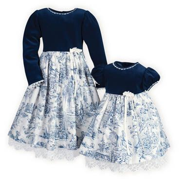 Matching sister dresses with delicate Venice lace trimmed navy stretch velour bodices atop cotton toile skirts. Attached petticoats with exquisite lace trim peeking out below hemlines. Button backs. Tie back sashes. Machine wash. USA made exclusively for THE WOODEN SOLDIER.