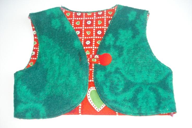 korte bodywarmer  gemaakt van een deken   gevoerd met een retro stof met patroon  sluit met 1 knoop   op de rug een rode appel